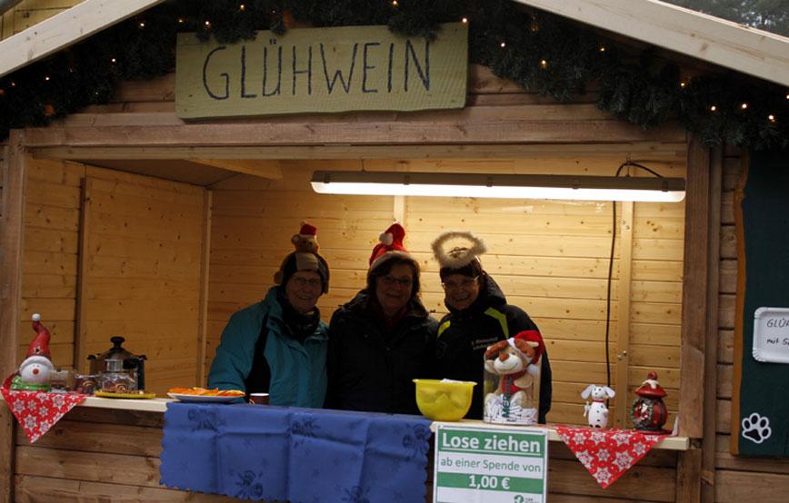 Tierweihnacht-drei-frauen-im-Glühweinstand-holzhütte Tierschutzliga-Dorf